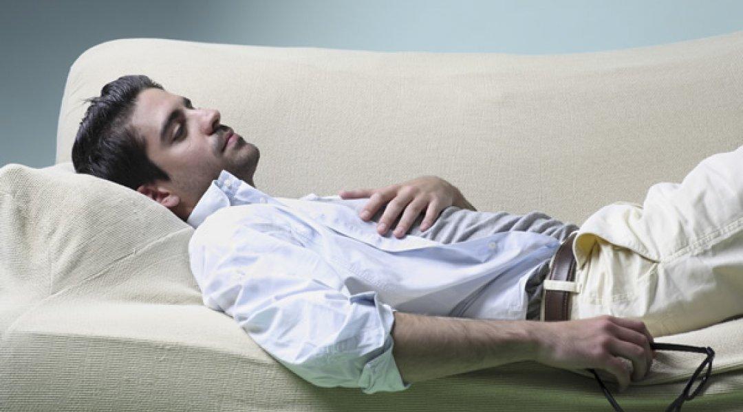 Homem pensativo deitado no sofa