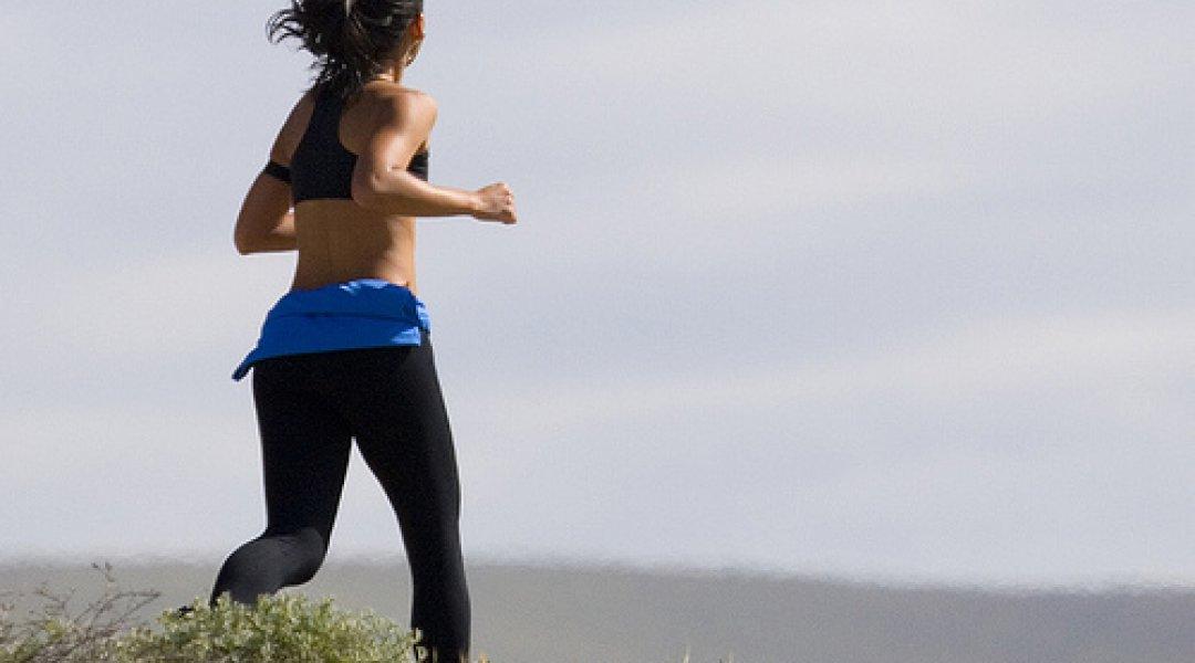 Mulher a fazer jogging na praia