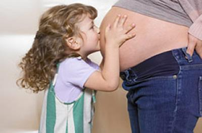 Filha beija a barriga da mãe grávida