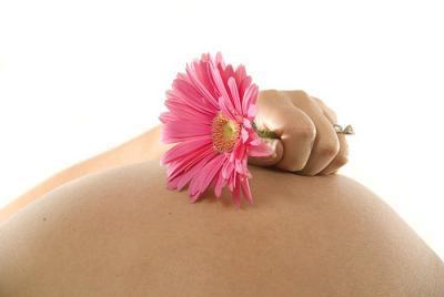 Flor em cima da barriga de uma grávida